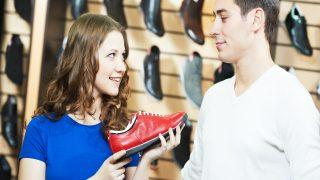 seller female assistant demonstrate shoes to young man during fo